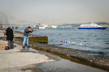 istanbul beach: Istanbul, Turkey - April 08, 2016: Man is shooting balloons on the water of Bosphorus in Istanbul, Turkey