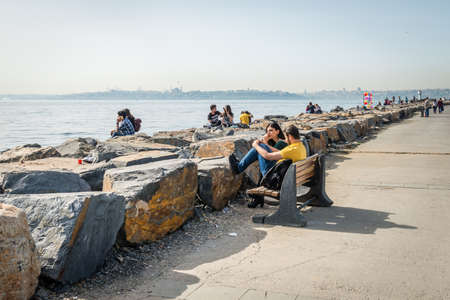 kadikoy: Istanbul, Turkey - April 18, 2016: Young couple is sitting at seaside in Kadikoy, Istanbul, Turkey