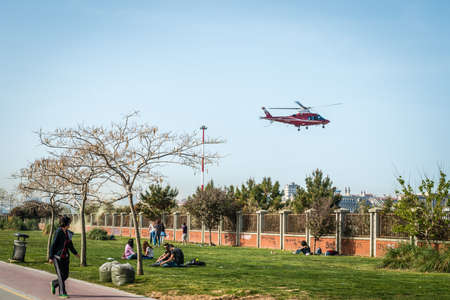 passing over: Istanbul, Turkey - April 18, 2016: Young people are sitting at seaside in Kadikoy while helicopter is passing over in Istanbul, Turkey Editorial