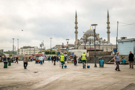 eminonu: Istanbul, Turkey - April 20, 2016: People are walking near the Eminonu port on the background of New mosque in Istanbul, Turkey