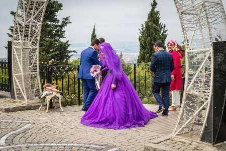 Istanbul, Turkey - April 23, 2016: Turkish bride with groom came on the top of the Camlica hill to enjoy the view and take some photos in Istanbul, Turkey