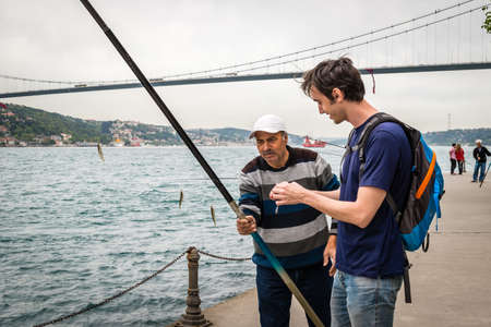istanbul beach: Istanbul, Turkey - April 23, 2016: Local fisherman is offering his rod to the tourist to take a photo in Istanbul, Turkey