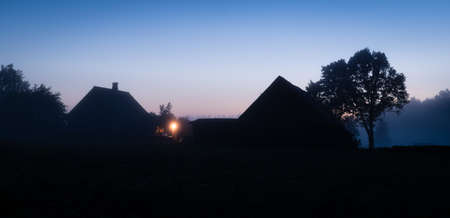 panoramatic: Rural landscape. Silhouettes of Latvian farmhouse at sunset