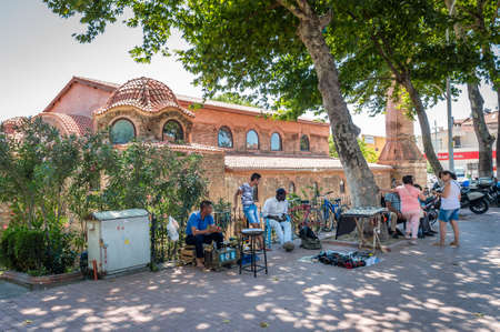 aya sofia: Iznik, Turkey - July 23, 2016: Street sellers sitting in the street near Aya Sofya also known as Hagia Sophia in Iznik, Turkey