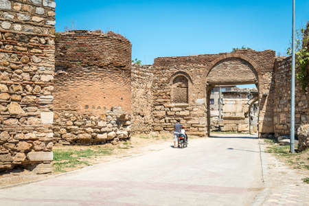 Iznik, Turkey - July 24, 2016: Father and son are passing by walls of Yenisehir gate of Nicea Ancient City, Iznik