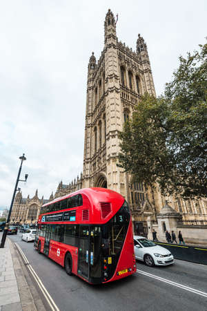 London, United Kingdom - October 20, 2016: Cars are passing by the Palace of Westminster which is the meeting place of the House of Commons and the House of Lords, the two houses of the Parliament of the United Kingdom