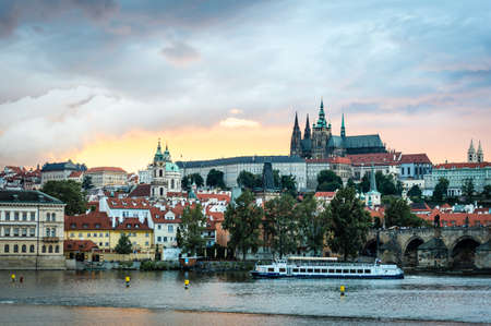 Sunset over Vltava river with the view to the Prague Castle and Charles bridge in Czech Republic