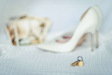 Greeting card of wedding, two locks symbolizing true love and white bridal shoes 版權商用圖片
