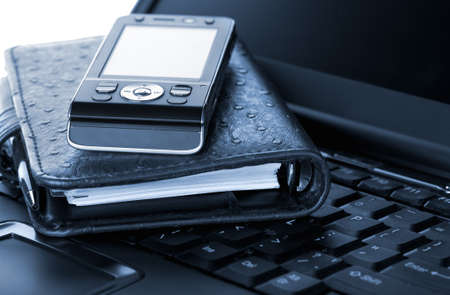 Organizer and mobile phone laying on laptop Stock Photo