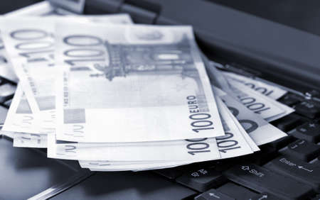 Euro banknotes on laptop toned blue