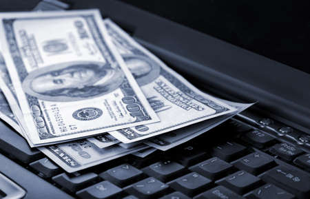 American dollars laying on laptop toned blue Stock Photo