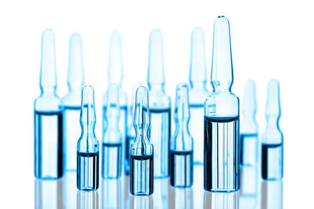 Different medical ampoules toned blue isolated on white photo