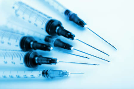 Closeup of syringes toned blue  Selective focus on the needle tips  For medical and laboratory themes
