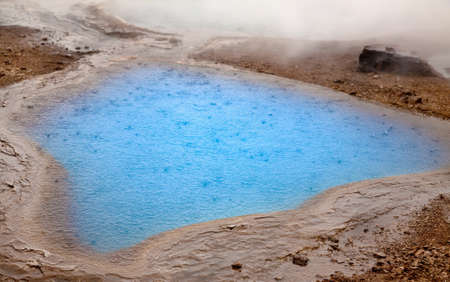 Pool with bright blue hot water at the Haukadalur geyser area in Iceland  Stock Photo
