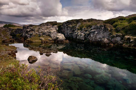rift: Deep fissure Flosagja with crystal clear cold water at Thingvellir National Park  The fissure in the earth