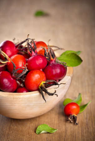 Red rose hips with green leaves in wooden bowl photo