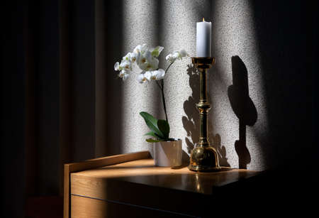 Burning candle, white orchid flowers and shadows on the wall - fragment of church interior