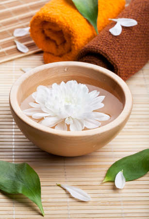 Towels and white daisy in wooden bowl  Spa and body care  photo