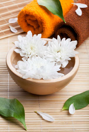 Towels and white daisies in wooden bowl  Spa and body care  photo