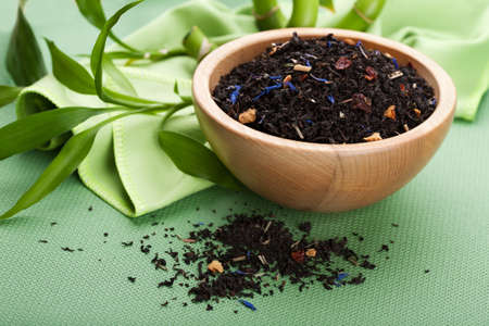Dry black tea with rose hips and cornflower petals in wooden bowl Stock Photo