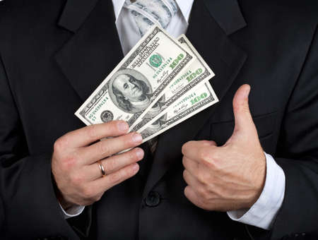 Businessman holding dollar banknotes and making his thumb up