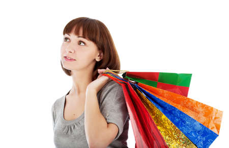 Pensive young woman with colored shopping bags, isolated on white Stock Photo
