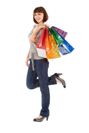Smiling young woman with rainbow colored shopping bags isolated on white Stock Photo