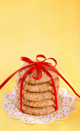Stack of ginger cookies tied with red ribbon on yellow background photo