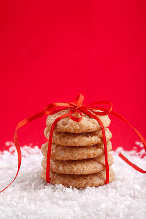 Christmas ginger cookies tied with red ribbon on the snow