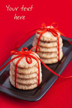 Cookies tied with red ribbon on black plate photo
