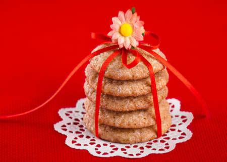 galletas de jengibre: Galletas de jengibre atadas con cinta roja sobre fondo rojo Foto de archivo