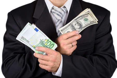 corporate greed: Businessman holding dollars and euros, isolated