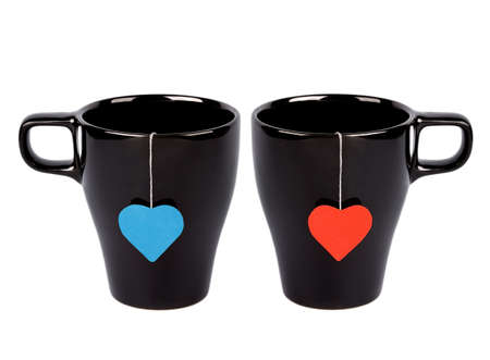 english breakfast: Tea bags with red and blue heart-shaped lables in black cups isolated on white. For him and for her.