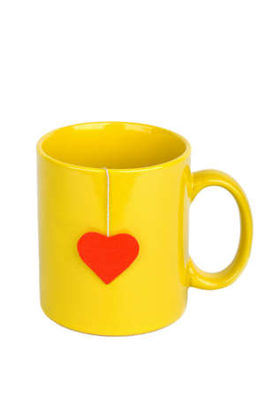 Tea bag with red heart-shaped label in yellow cup isolated on white photo