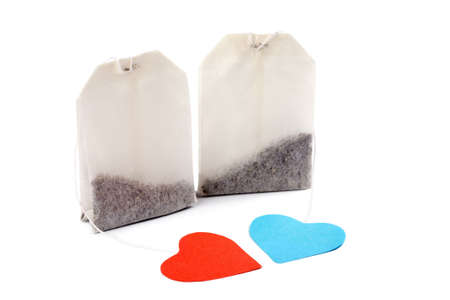 Two tea bags with heart-shaped blue and red labels isolated on white. For him and for her photo