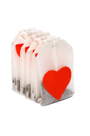 Tea bags with heart-shaped red lables isolated on white Stock Photo