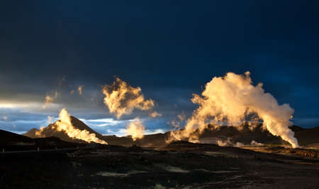 Steam erupting from geothermal power station at sunset, yellow light of setting sun back-lighting the columns of steam, Myvatn area, Iceland Stock Photo