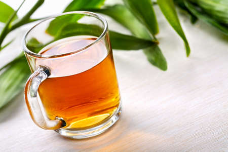 Cup of black tea and green leaves