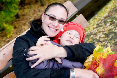 Mother and child sitting on a bench in autumnal park Stock Photo