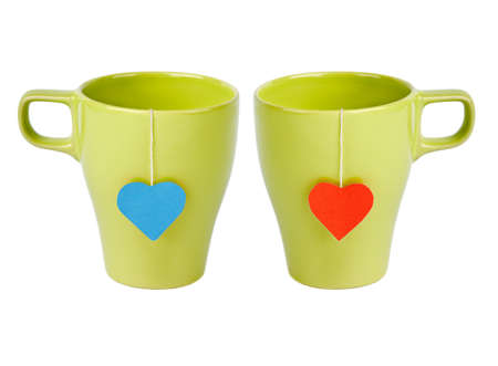 Tea bags with red and blue heart-shaped lables in green cups isolated on white. Tea for two