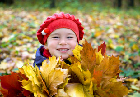 Little girl with autumn leaves in the park