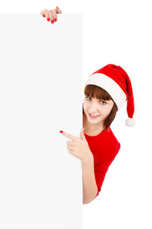 Smiling woman in Santa red hat pointing on blank sign billboard, isolated on white photo