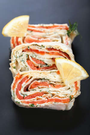 Roll with smoked salmon, cream cheese and dill on black background