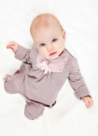 Sweet little baby girl in striped pink costume laying on white background. Top view. Stock Photo