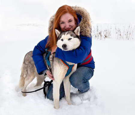 Young red-haired smiling woman and dog siberian husky in winter