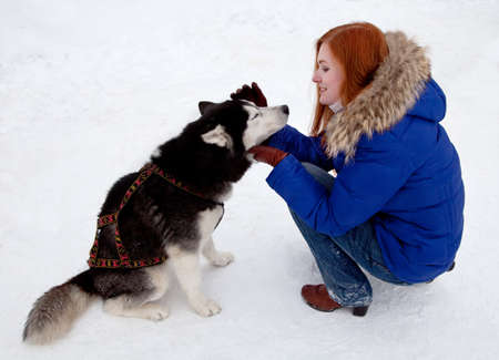 Young red-haired woman and dog siberian husky in winter