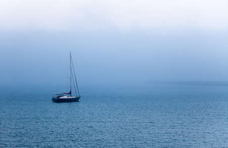 Sail boat in the morning fog 스톡 콘텐츠