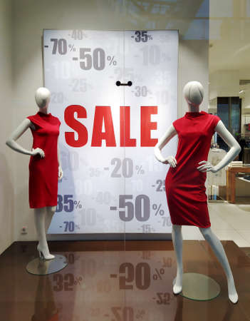 Text Sale on white poster and two mannequins standing In store window display of women's red dresses in shopping mall. Shopping, sale concept.
