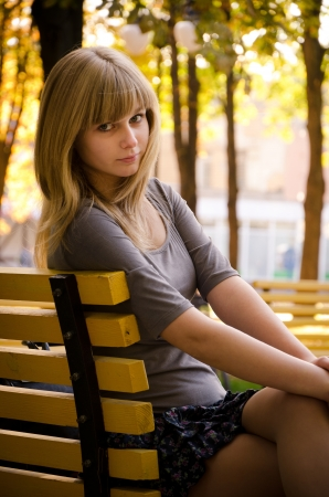 Girl sitting on a bench in a park photo