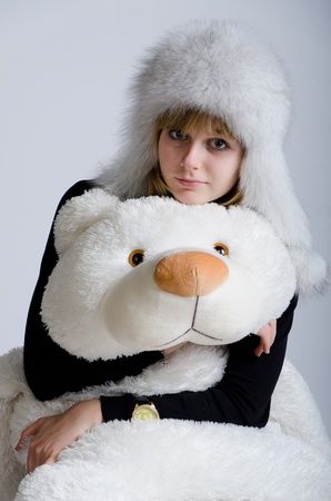 Girl in a white fur hat with a toy bear in a studio photo